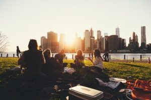 We are Wired to Need Each Other, a group of friends having a picnic with the setting sun and the city as a backdrop