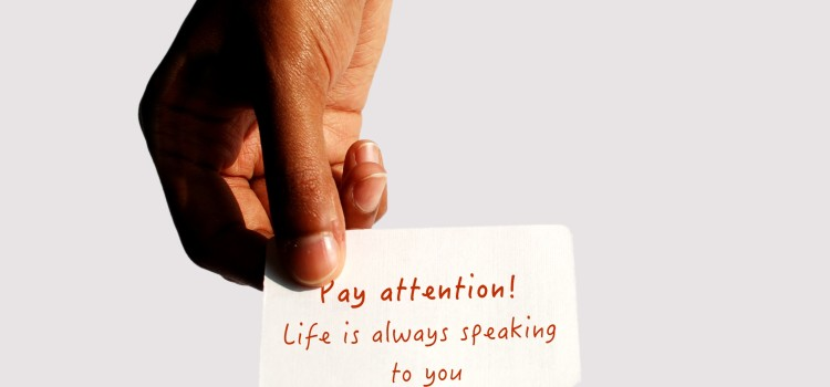 Hand holding out a card that reads: Pay attention, life is always speaking to you